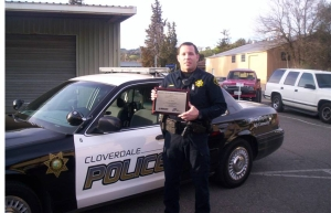 A police officer holding a plaque standing next to a police cruiser