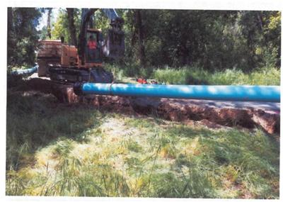 A piece of heavy equipment working on a large pipe